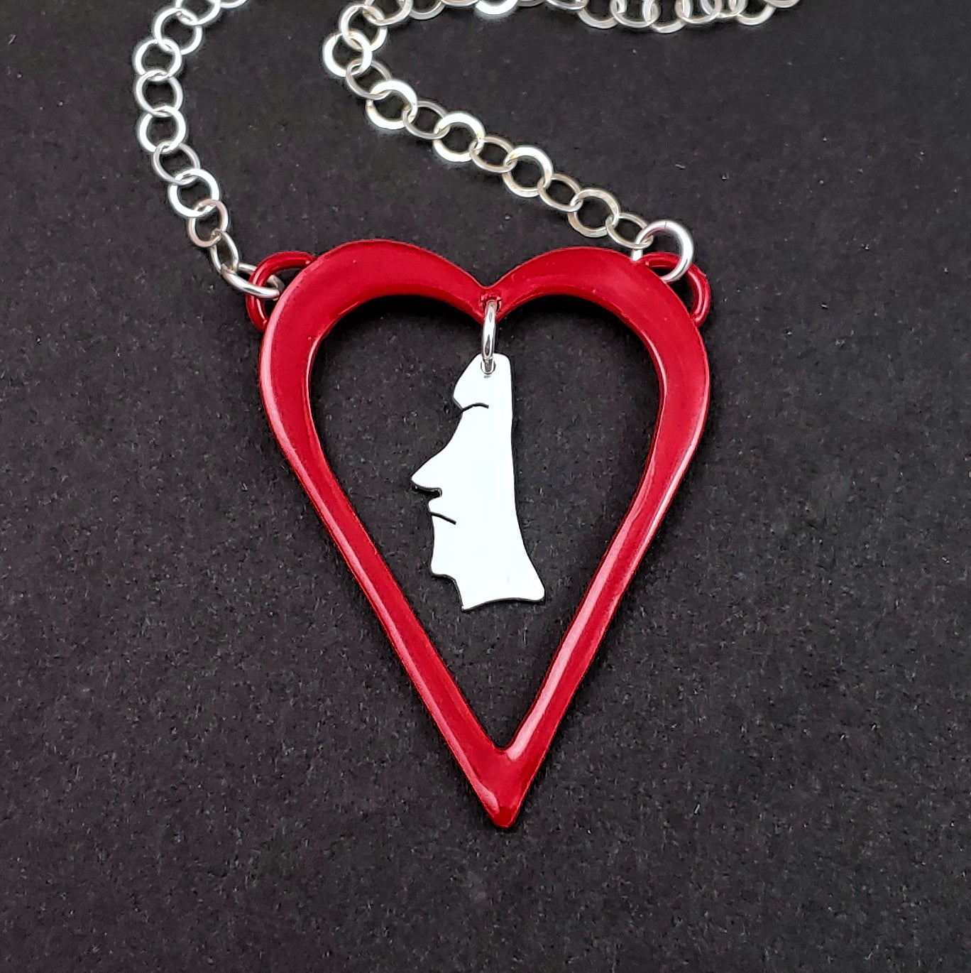 Red heart shaped necklace with sterling silver moai head in the middle