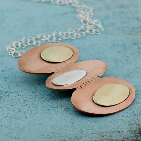 Modernist inspired ovals in copper, brass, and silver.