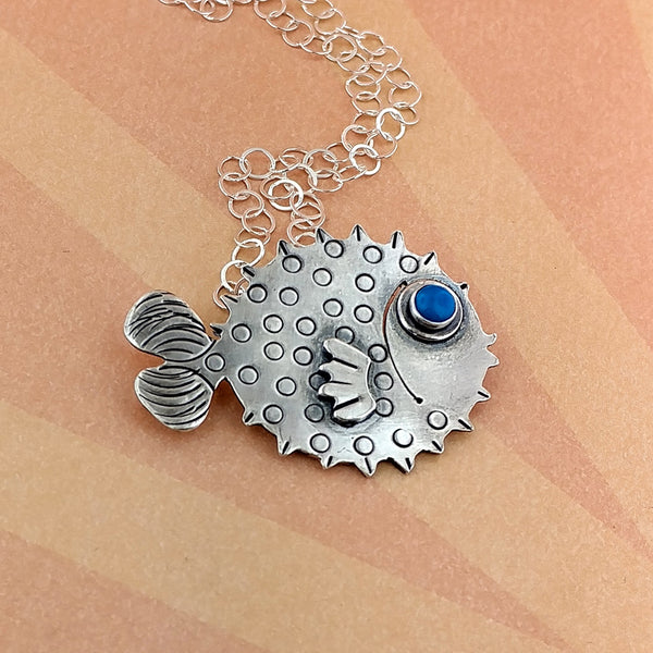 Puffer fish with gemstone eye made of sterling silver.