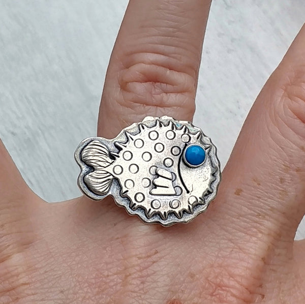 Pufferfish ring with blue howlite eye shown on ring finger