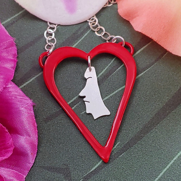 Powdercoated red heart shaped necklace with sterling silver moai dangling from the center