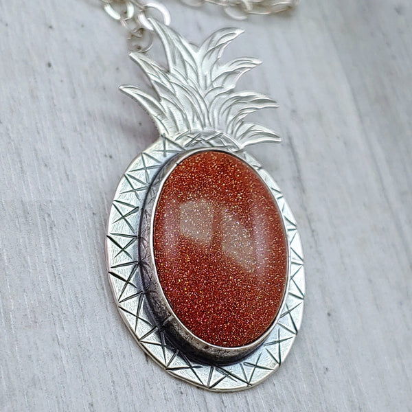 closeup of brown orange shimmery goldstone pineapple necklace in sterling silver