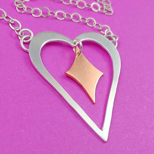 Heart shaped sterling silver necklace with a copper retro diamond dangling from the center