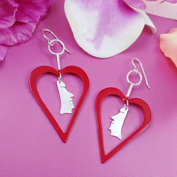 Red powdercoated heart shaped earrings with sterling silver moai heads in the center