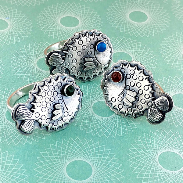 A trio of pufferfish rings with gemstone eyes
