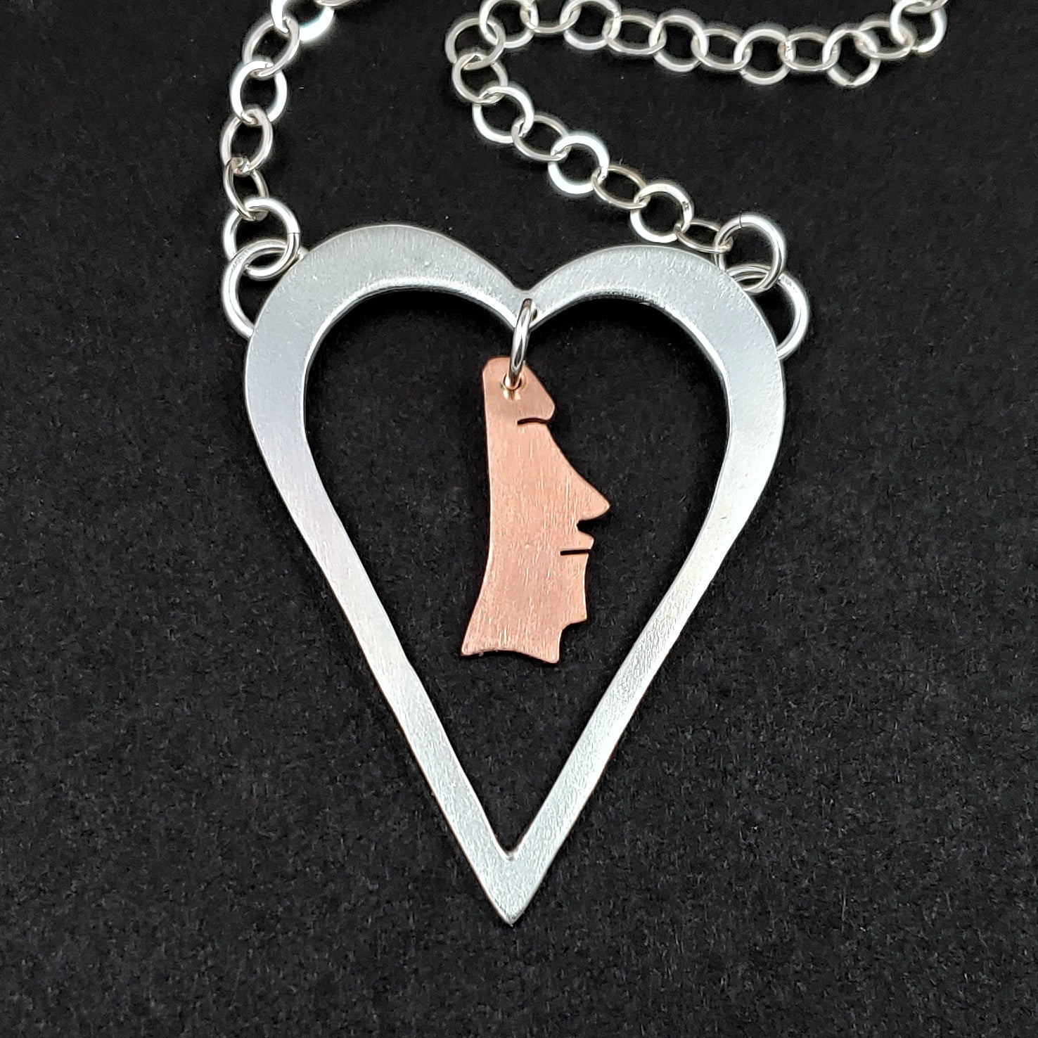 Sterling silver heart necklace with a copper moai head in the middle