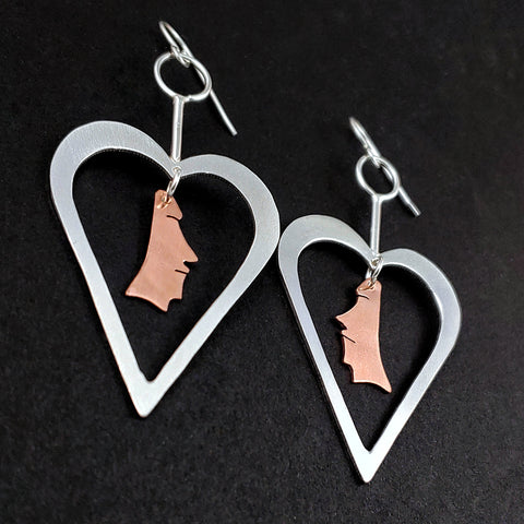 Sterling silver heart shaped earrings with copper moai heads in the middle
