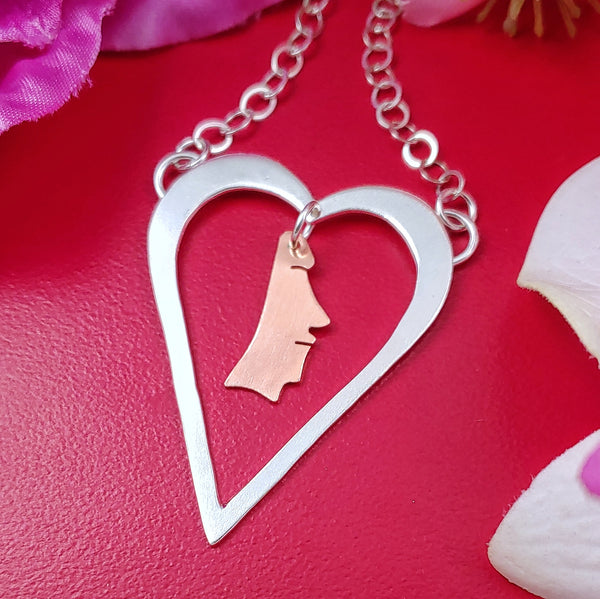 Sterling silver heart shaped necklace with a copper moai head dangling from the middle