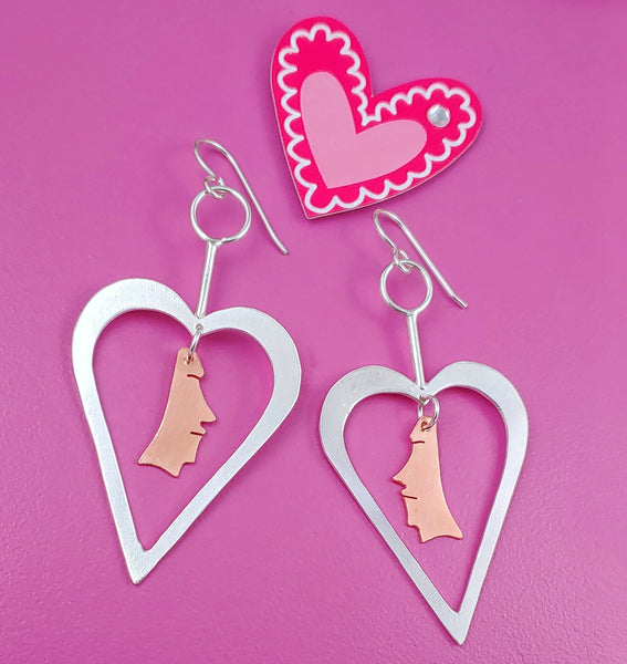 Sterling silver heart shaped earrings with copper necklace dangling from the centers