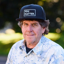 Matter Apparel You Matter design embroidered black and white 5 panel snapback trucker hat