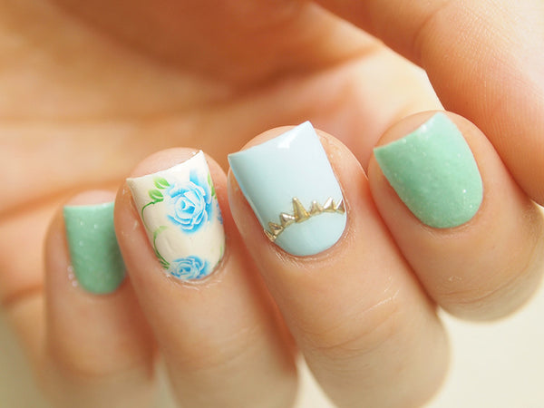 floral manicure with small silver nail art triangles