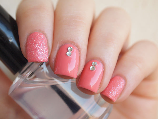 coral color manicure with clear nail rhinestones