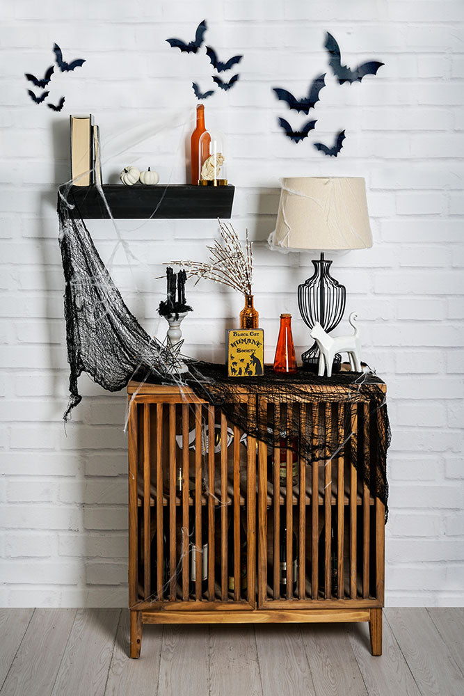 Minimal Halloween decor on a black wedge shelf and slated bar cabinet. Decorations include bats on the wall, black metal thick gauge wire lamp, spider webs, black webbing, ceramic cat figurine, and various bottles