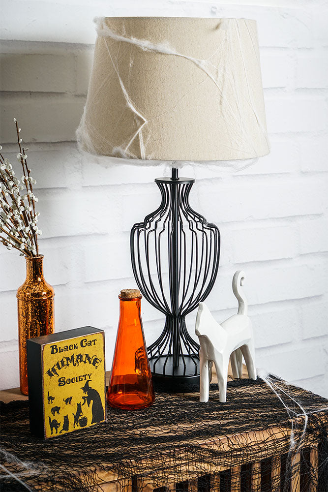 Black metal cage lamp on a wood slated cabinet surrounded by halloween decor including black webbing, spiderwebs on lampshade, orange bottles, plaque about black cats, and white ceramic cat statue