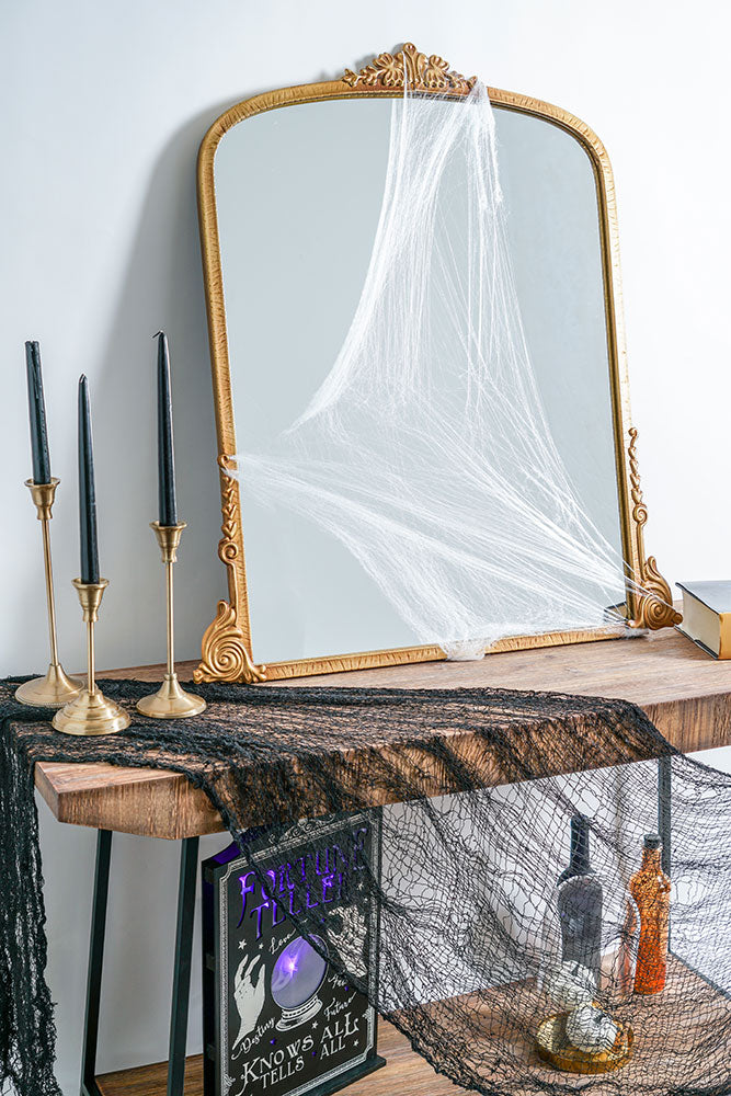 Head West Mirror ornate gold color mirror on console table with Halloween decorations and gold candlesticks