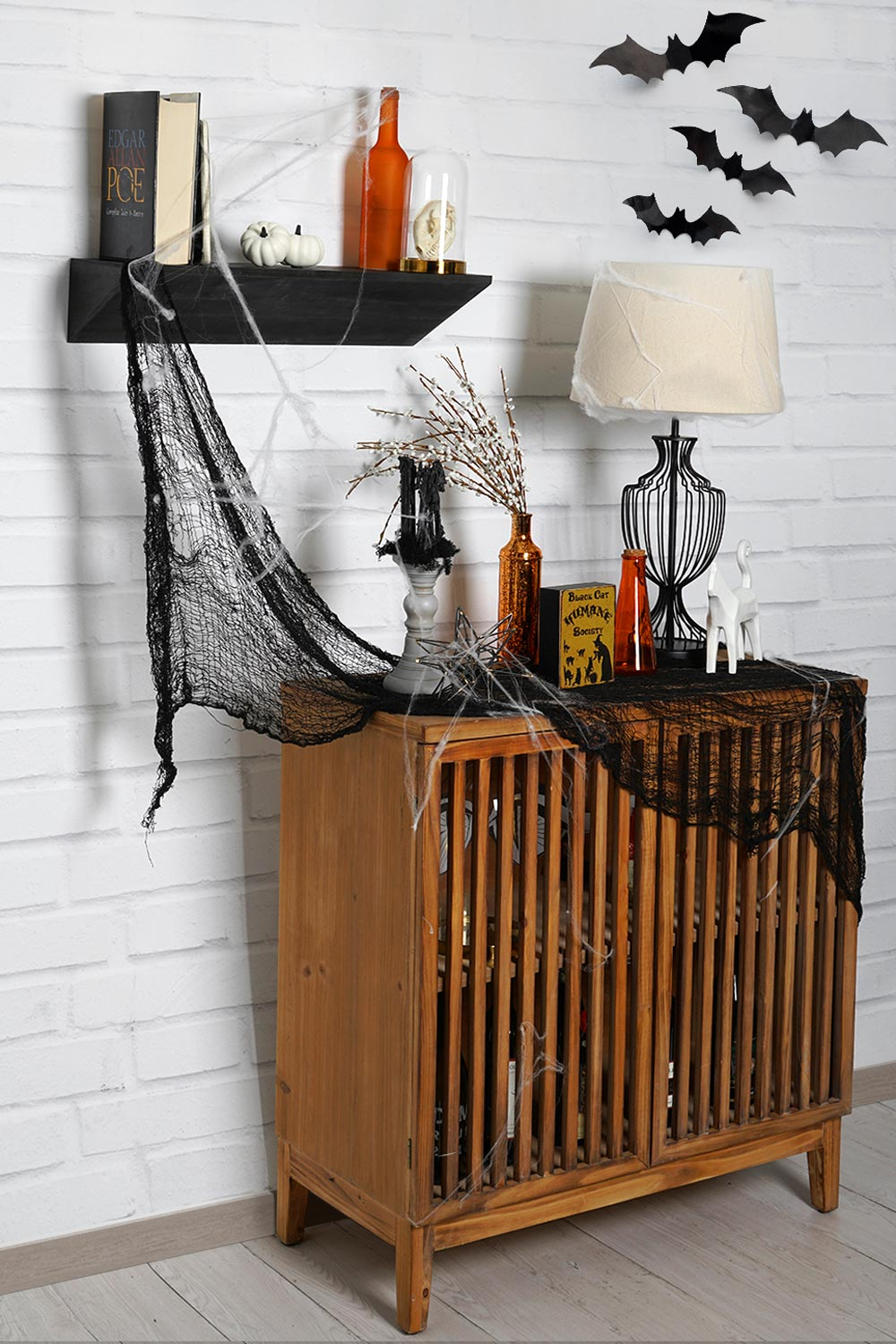 3/4 view of black wedge shelf with books and orange glass jars above a wood slated cabinet. Various Halloween decorations are on top of the cabinet and black bats are in upper right corner