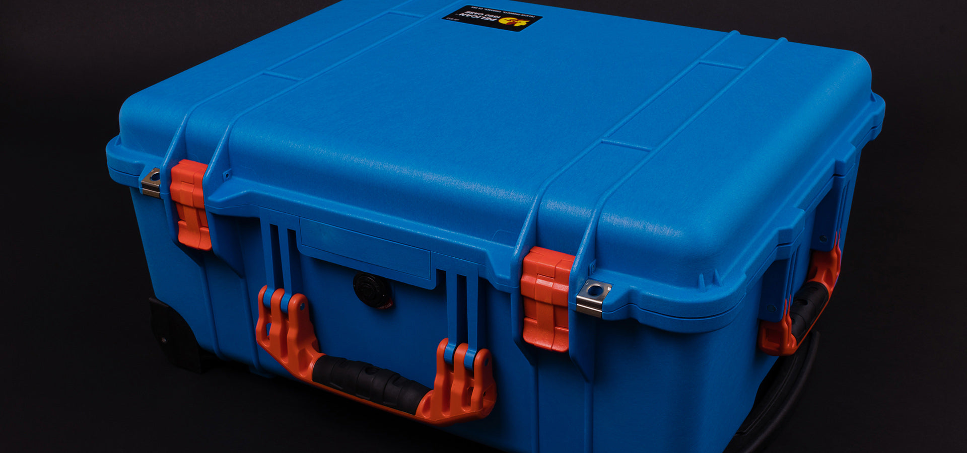 Blue Pelican 1560 Case with Orange Handles and Latches on Black Background