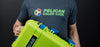 Man in Pelican Color Case T-Shirt Holding Lime Green Pelican 1510 with Blue Handles and Latches