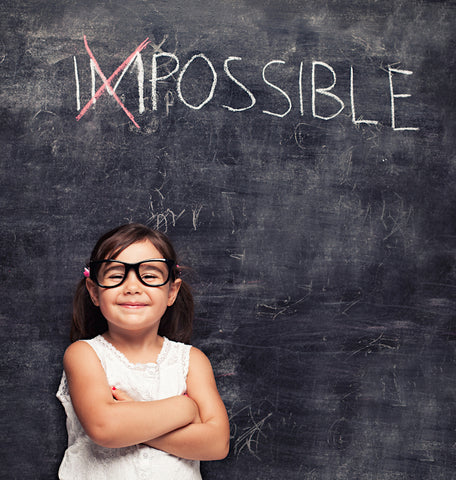 "elementary age girl in front of a chalkboard with the word ""impossible."" The ""Im"" in ""impossible"" is crossed out."