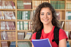 high-school girl holding books smiling at the camera