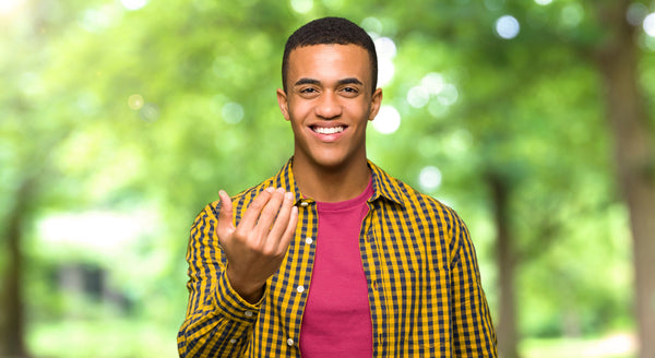 Male teen inviting viewer with hand gesture