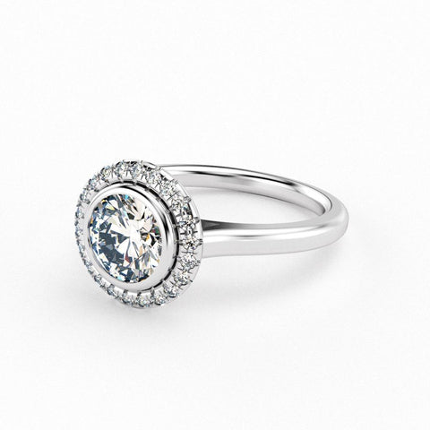 Christine Alaniz Designs custom engagement ring in platinum with a round, bezel set center and a simple split prong halo