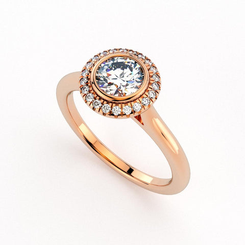 Christine Alaniz Designs rose gold engagement ring with a round brilliant diamond in a bezel setting, a pavé halo, and a plain shank