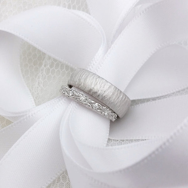 White gold and diamond eternity wedding ring with floral engraving, next to a wide wedding ring with a hand carved line texture. Both rings have white ribbon threaded through them.