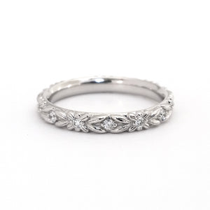 White gold and diamond eternity wedding ring with floral engraving, on a white background.