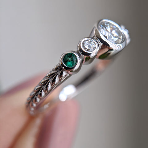 Diamond and emerald ring, stones set in bezels, with braid engraving on the shank. The ring is held by a hand with pale pink nails.