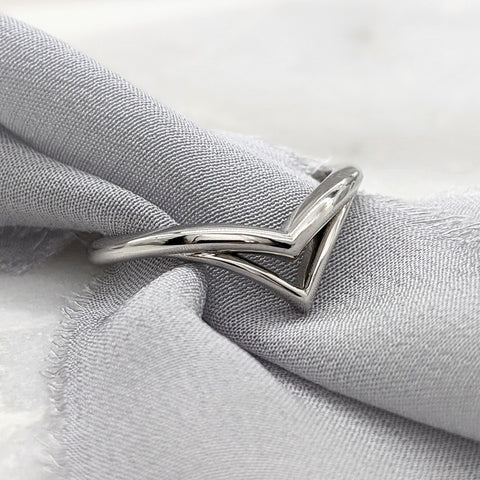 Double chevron wedding ring in white gold with a gray silk ribbon slipped inside it.