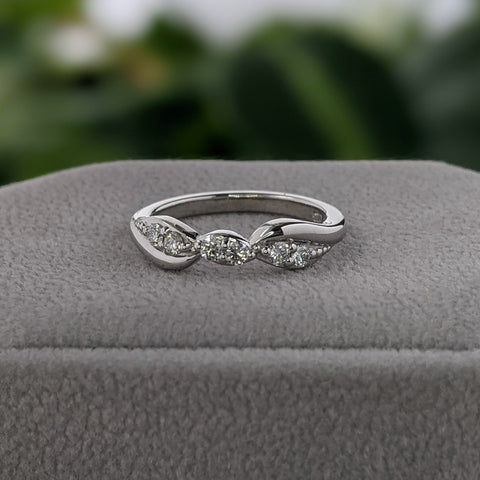 White gold and diamond wedding ring on a gray suede box, with green leaves in the background.