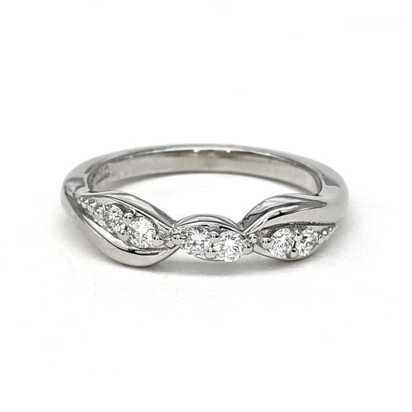 White gold and diamond bypass style wedding ring sitting on a white background.