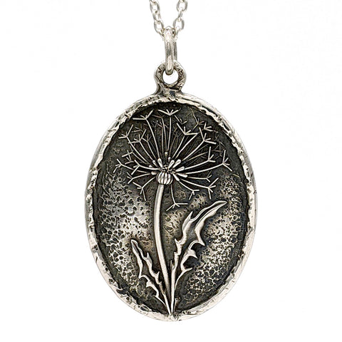 Chunky oval necklace in sterling silver that features a dandelion flower with two leaves. It has a rustic, hand-carved texture and a oxidzed finish.
