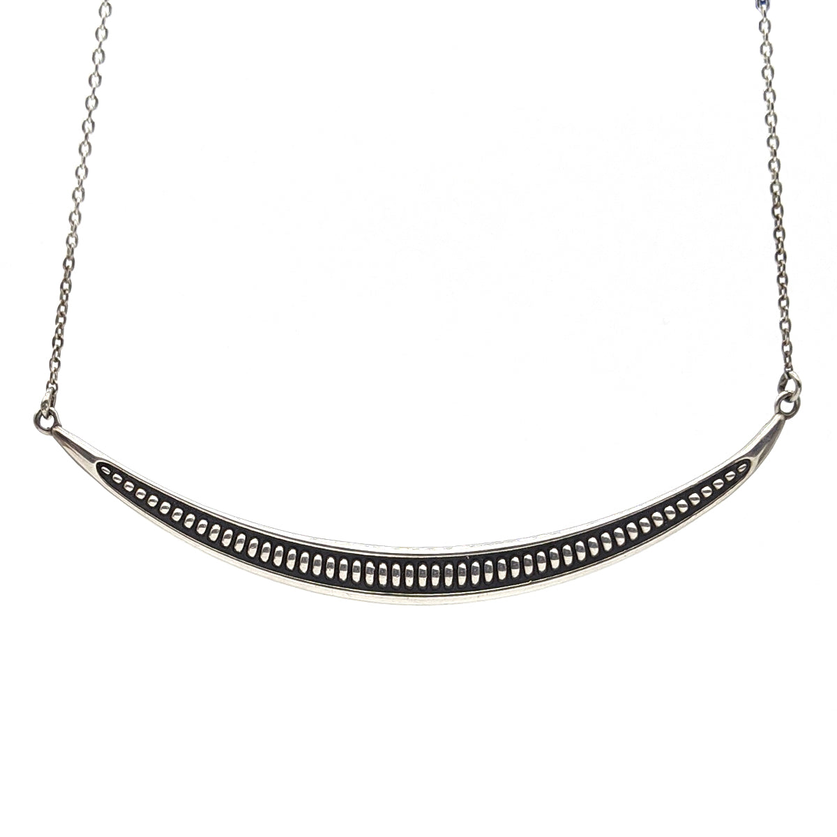 This is a sterling silver arc necklace that has a ribbed texture and a oxidized finish in the background to highlight that texture.