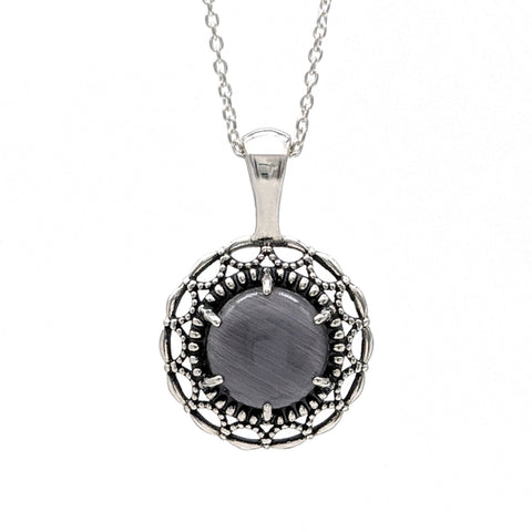 Sterling silver necklace with a scalloped and beaded halo border. It features a black glass cabochon in the center.