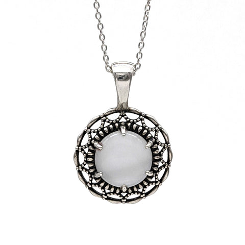 Oxidized sterling silver pendant with a scalloped and beaded halo border. It features a white glass cabochon gemstone in the center.