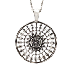 Large coin medallion pendant with a protea flower design radiating from the center.