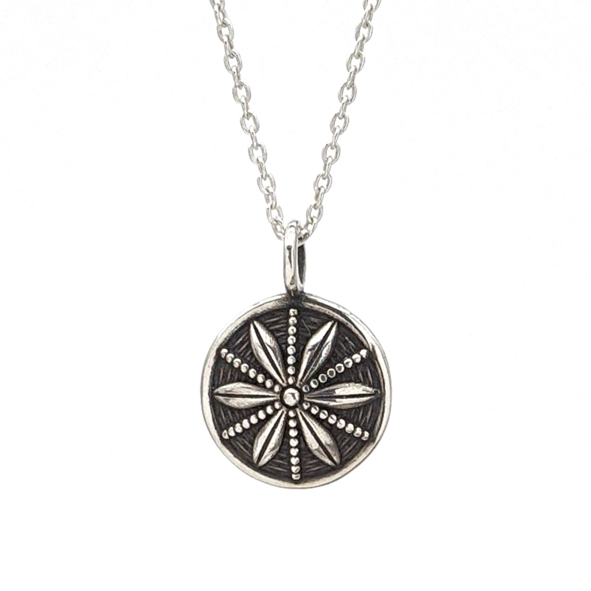 Tiny sterling silver circle pendant with a star anise design radiating around the center.