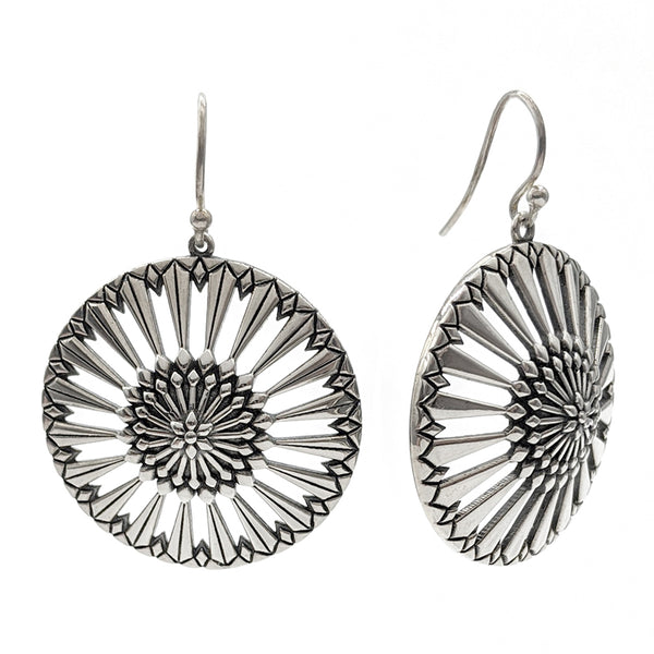 Sterling silver large circle earrings with pierced openings and oxidized background to highlight the textures.