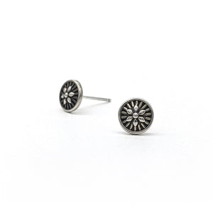 Tiny sterling silver stud earings with a whorl pattern in the center.
