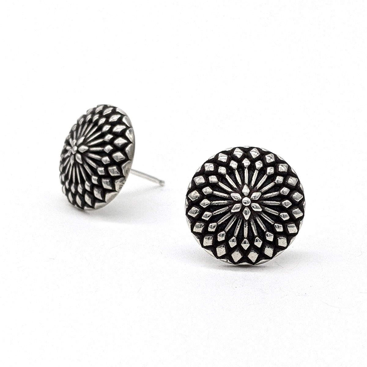 Sterling silver domed stud earrings with a whorl pattern of diamond shapes, highlighted by an oxidized background.