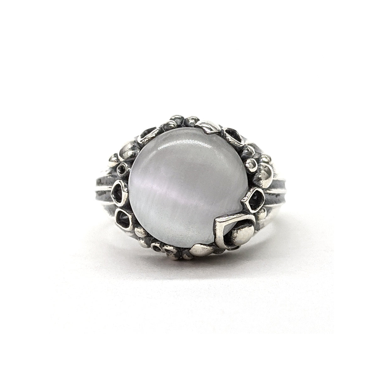 Sterling silver ring with an oxidized finished in the recesses. This statement cocktail ring features a white glass cabochon gemstone in the center.