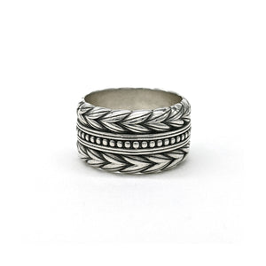 Wide band in sterling silver with braided bands on the outside and a row of beads along the center.