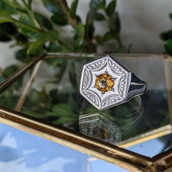 Silver hexagon shaped ring with a yellow citrine gemstone in the center. The ring is sitting on a piece of glass, in front of a branch with green leaves.