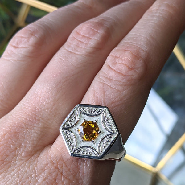 Silver hexagon shaped signet ring with a yellow citrine, worn on the index finger of a woman's hand.