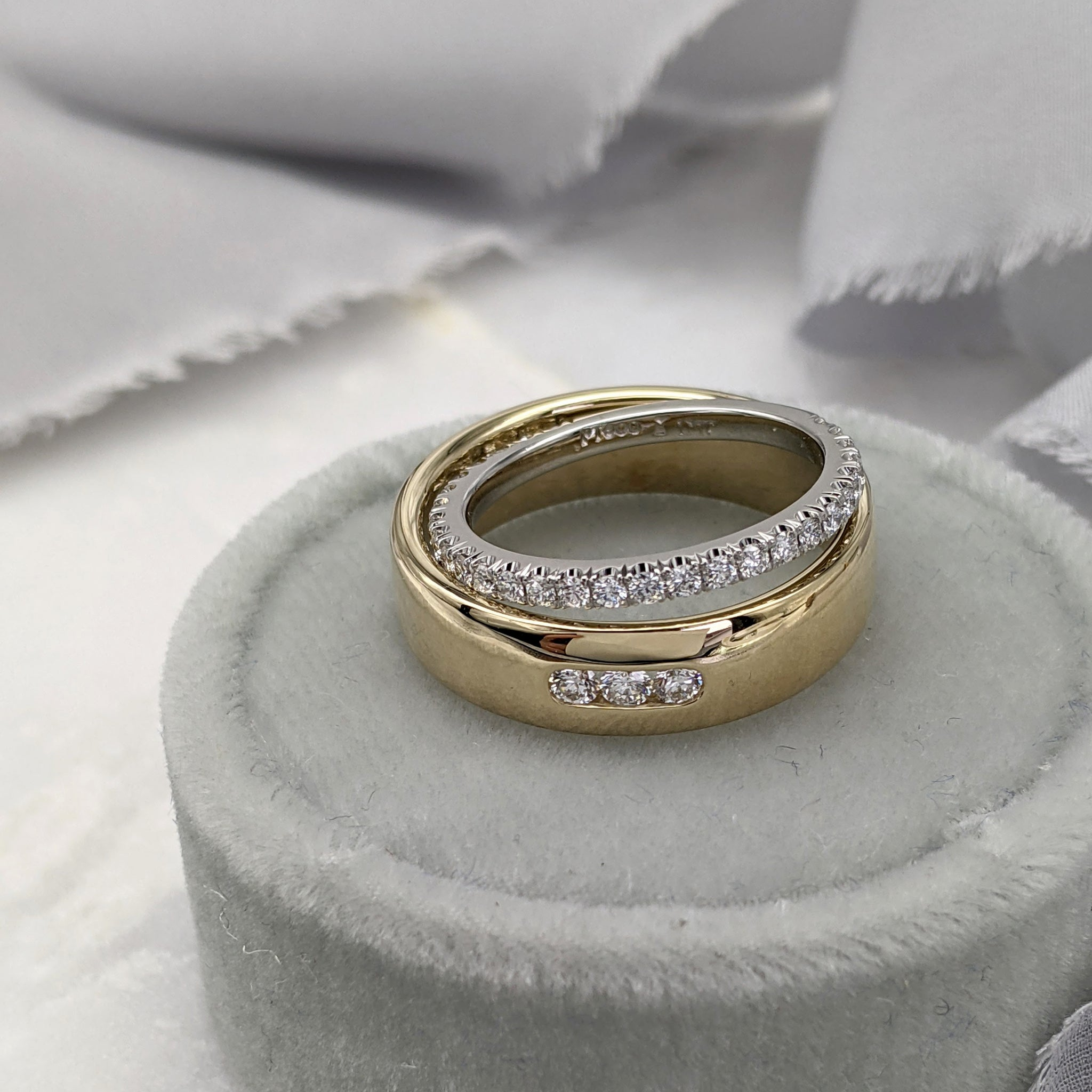 Yellow gold wedding ring with three channel set diamonds, with a platinum and diamond pavé wedding ring sitting on top of it. Both rings are in a gray velvet ring box, with gray ribbon in the background.