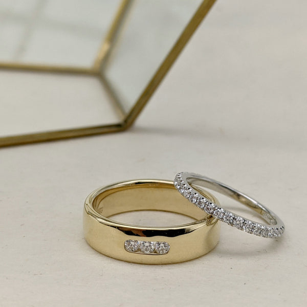 Yellow gold wedding ring with three channel set diamonds, with a platinum and diamond pavé wedding ring leaning against it. Rings are on a cream backgrop, with a geometric brass metal decoration in the background.