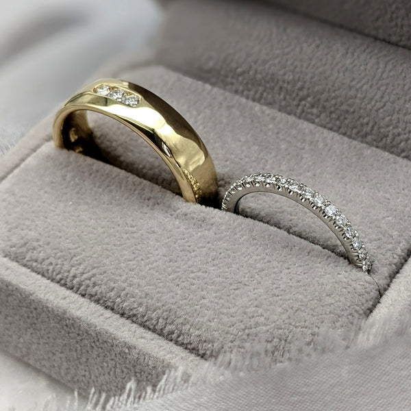 Yellow gold wedding ring with three channel set diamonds, with a platinum and diamond pavé wedding ring sitting on top of it. Both rings are in a gray velvet ring box, with gray ribbon in the foreground.