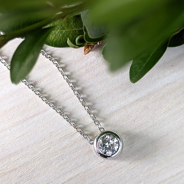 Round brilliant diamond set in a bezel setting, on a cable chain. The pendant sits atop a pine background, with green leaves along the top of the image.